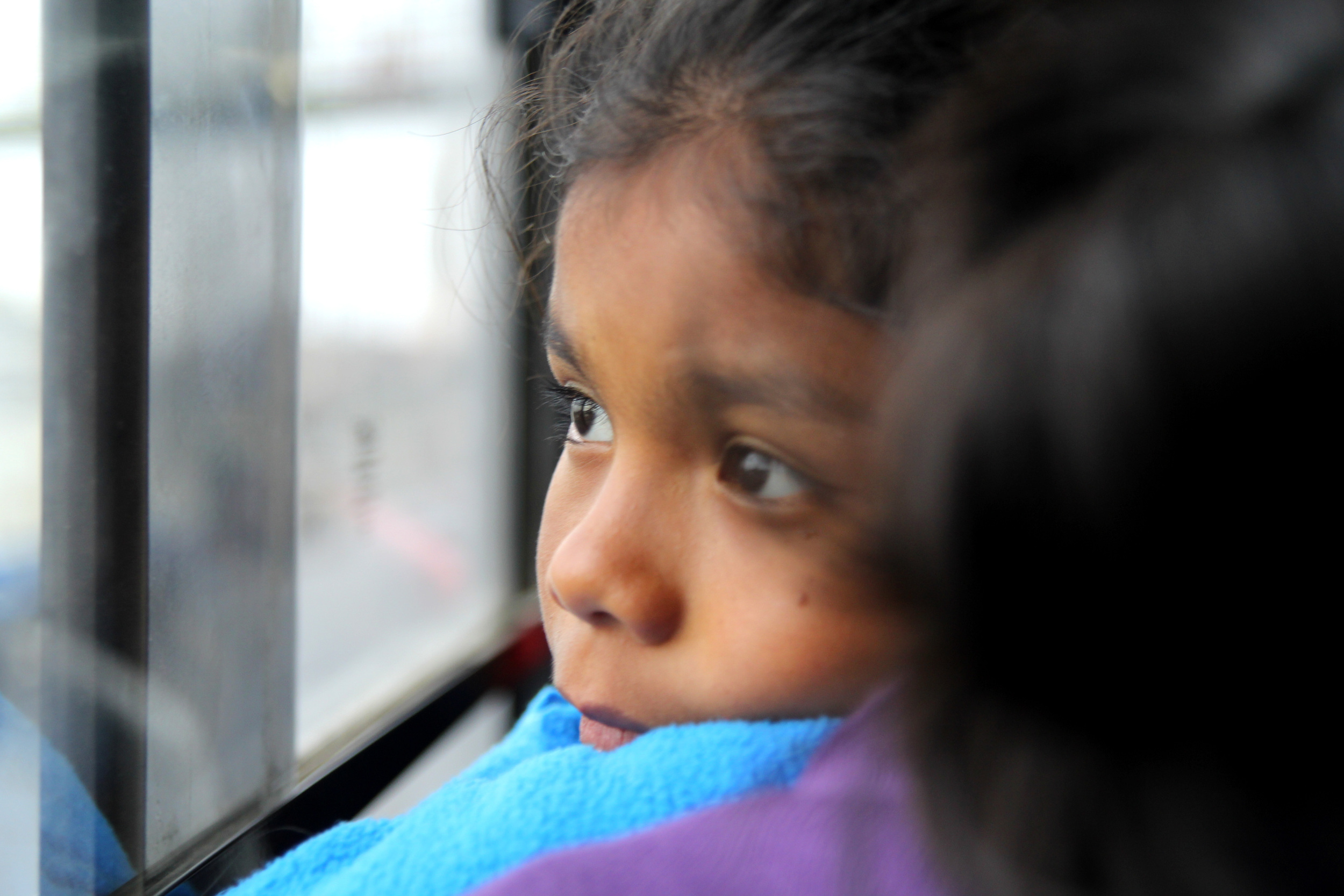 """A girl looking at the window on a """"micro"""" in Lima, Peru."""