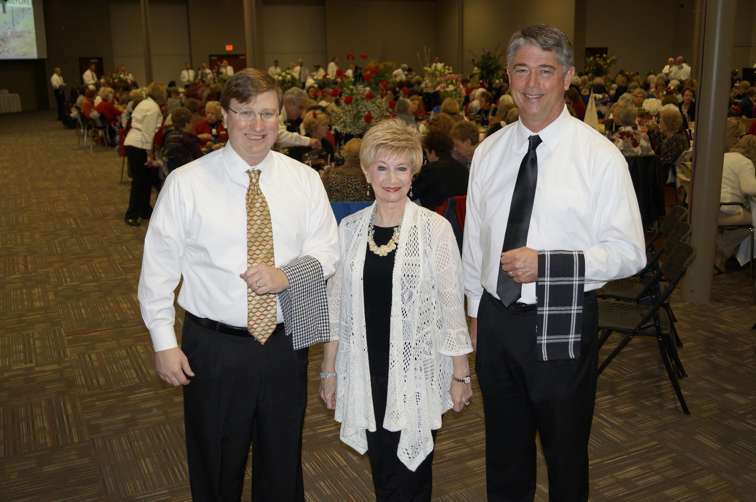 """Brandon Garden Club (BGC) had 44 """"celebrity"""" servers to wait on the 320 guestsat40uniquelydecorated  tables  . Servers pictured (l to r): Lt. Governor Tate Reeves, BGC President Charla Jordan, and Brandon Mayor Butch Lee."""