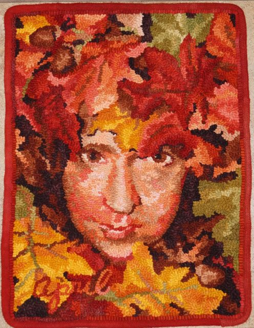 """Lady Red Jack  2011, September. Faces of the Seasons  Series. 15"""" by 19 1/2"""". #6 cut on linen. Designed, dyed and hooked by April DeConick. Red Jack Palette Wool: 8-value packs of Bittersweet 162, Peter Pumpkin 163, Ellendale Orange 126, Tanglewood 148, and Lake Agate 127; 1 piece of Goodfellow Yellow 105 value 5,Will 'O Wisp 158 value 5; Moorland Moss 106 dappled; 2 pieces of Sunset Gold 104 value 6; Goodfellow Yellow 105 value 7; Black Orchid 146 value 7 and 8; Will 'O Wisp 158 two textures; 4 pieces Nightshade Berry 160 four textures."""