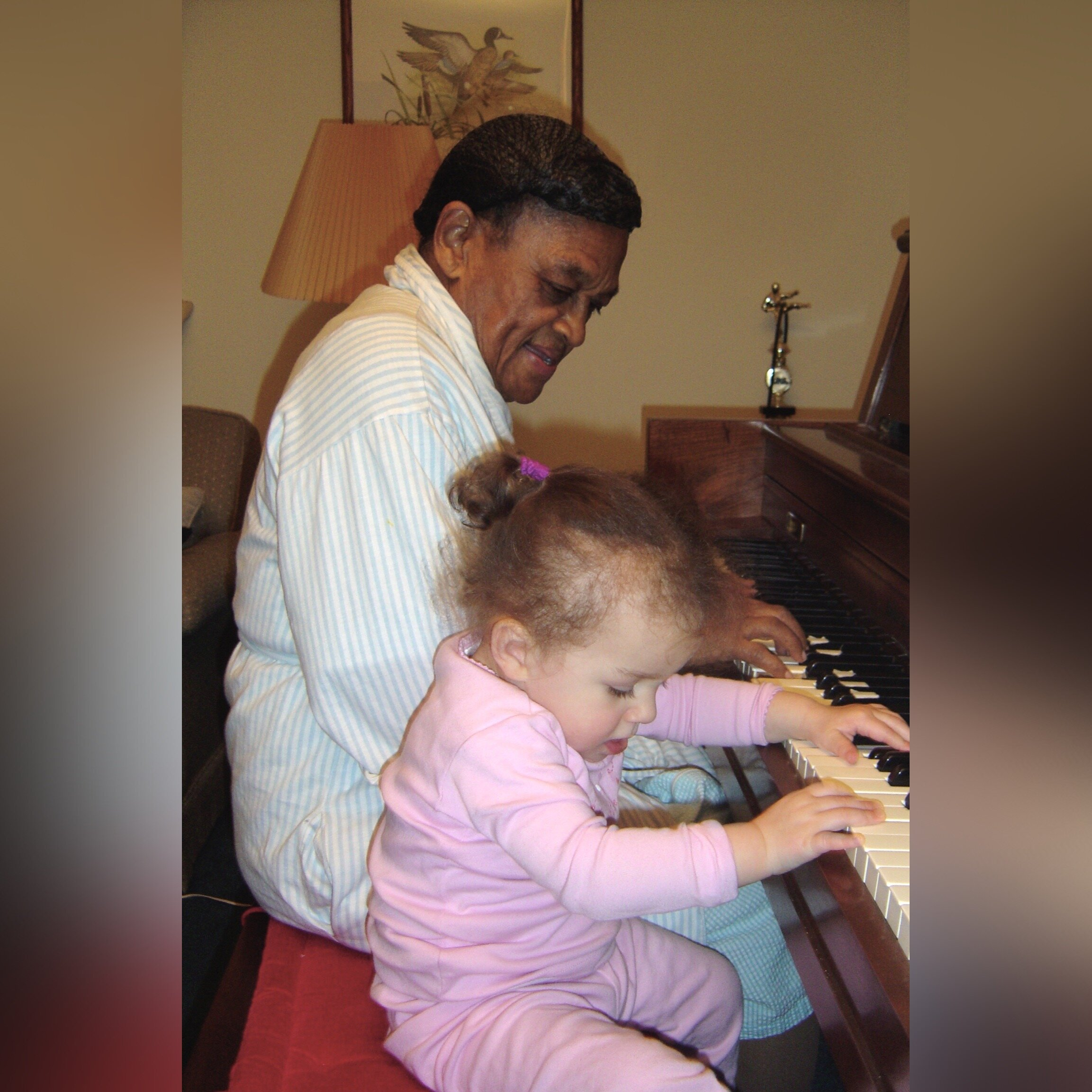 Mom playing the piano with Grace. Taken in 2006.