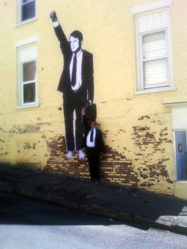 """Street view of Joel Richardson and his artwork for Occupy with Art's production """"Wall Street to Main Street"""" in Catskill, NY (2012)"""
