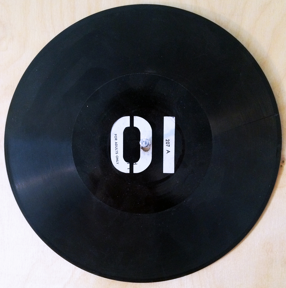 """Black 01 Vinyl"" Adhesive Vinyl on Vinyl Record 9.75"" in diameter 2001 $450  One of the Vinyl on Vinyl series produced for Heartless01, ""Black 01 Vinyl"" picked up a crack somewhere along the way. These discs referenced the amazing music recorded for our collective 01 projects in Nashville. In installations, the 01 vinyls operated visually in tandem with the environmental vinyl 01 sticker grids and other applications on objects (e.g., monitors, canvas, books, etc.) to dissolve encompassing architecture and produce new ontology for the elements in our 4D arrays, both virtual and analog, in new and traditional media."