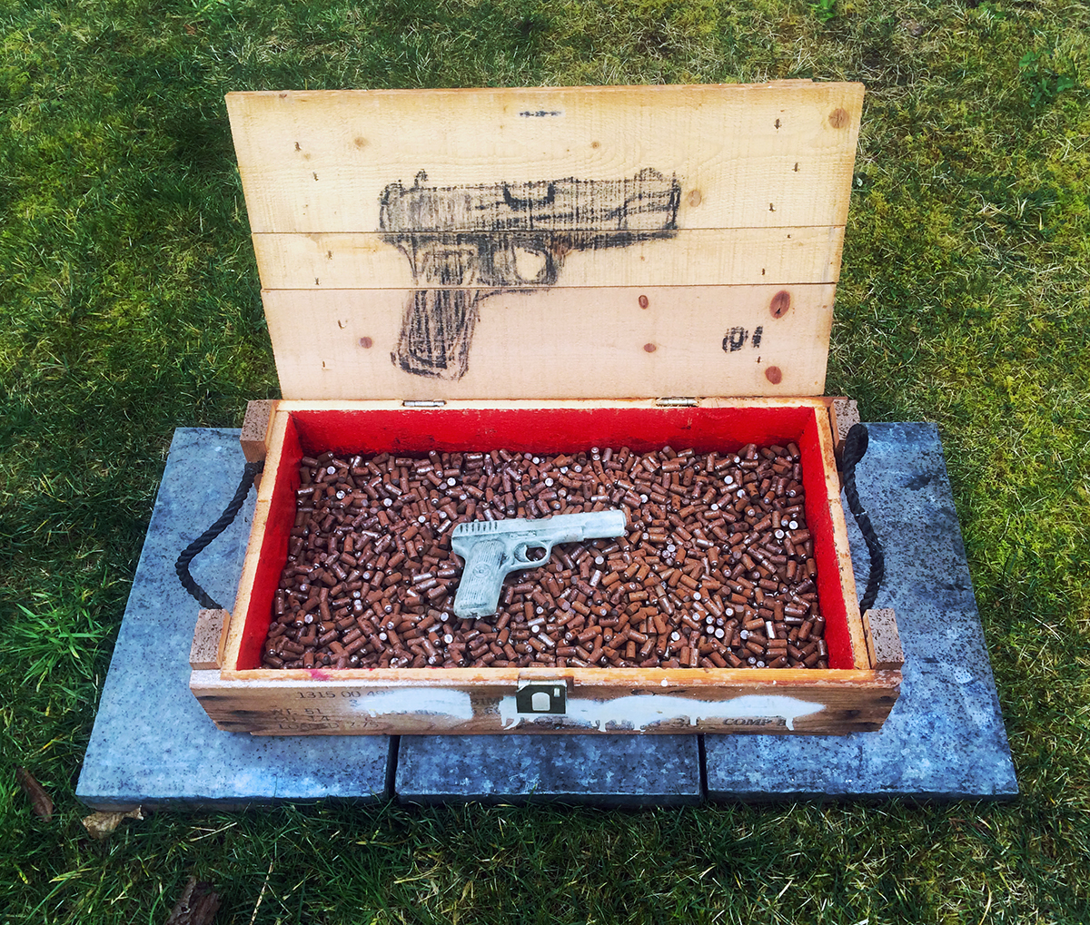 """Baudrillard [Simulation & Simulacra]"" Ammo Crate, Metal Slugs, Toy Gun, Acrylic Paint, Charcoal 18"" x 26"" x 14"" 2006 $2800  ""Baudrillard"" was initially exhibited in ""7 Episodes"" at the CGU art building Project Gallery. The reference to Baudrillard is a post-EGS titular superimposition. My appreciation of this 4D installation element grows with time. The pistol is a toy from my childhood, over-painted with luminescent acrylic. I believe I picked up the slugs in Austin. The charcoal was gathered after the Show Low wildfires. The crate came from that IE army surplus store where I acquired Army Joe."