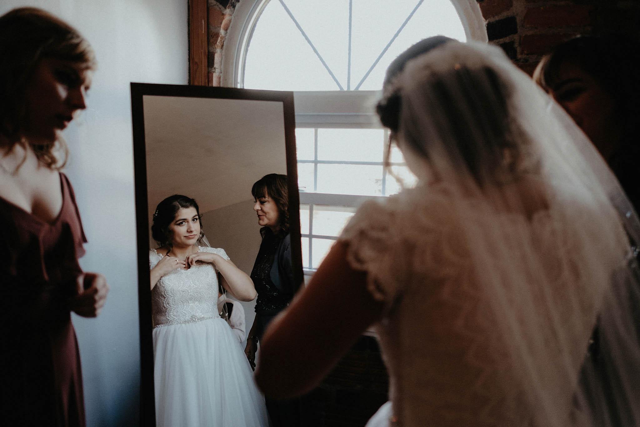 cincinnati warehouse wedding photographer bride putting on dress