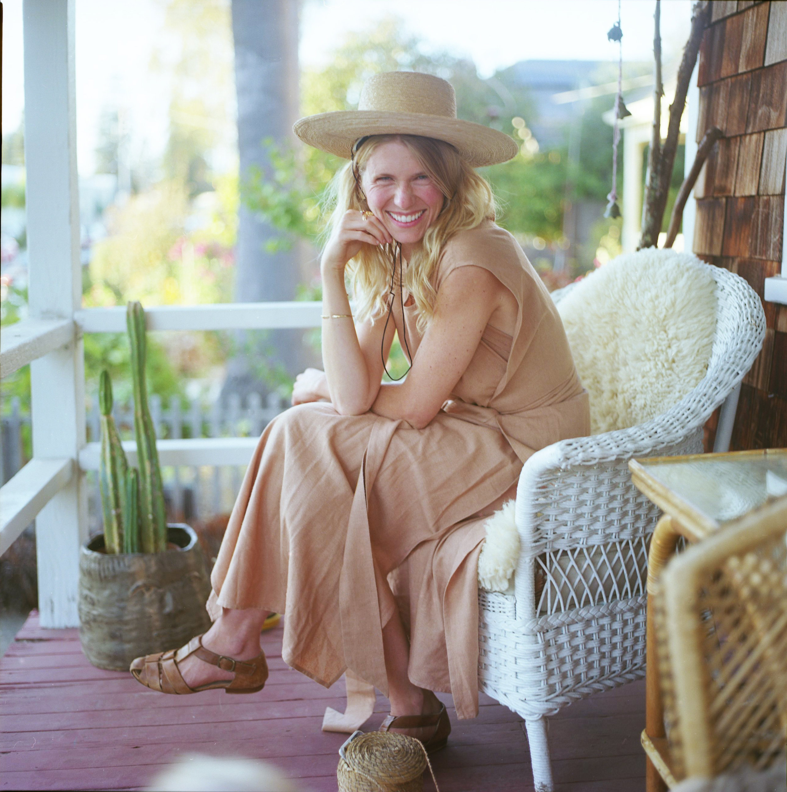 Shepherdess Kelci Potter smiles with pure joy on her front porch in Santa Cruz, California. Kelci hand crafts a line of solid gold stackers and unique pieces with spirit and soul as her cornerstones of a wildly successful and loved line.
