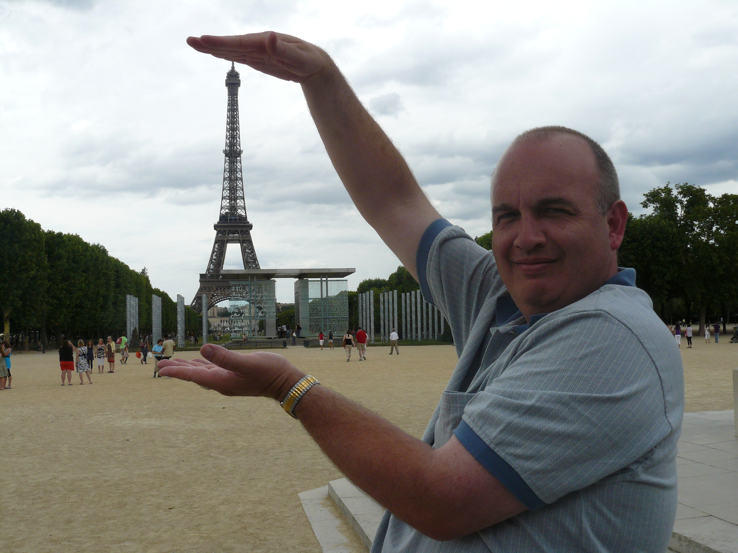 Our accompanist, Graham Adams, measuring the height of the Eiffel Tower before we go up to the top the next day.