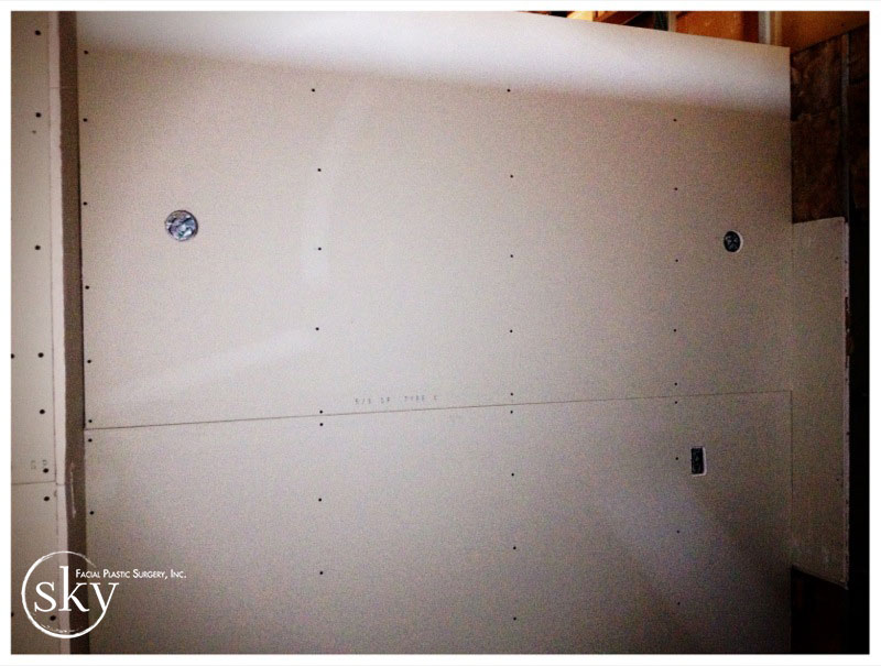 PHOTO: The drywall in the consultation room, with holes where the sconces will be placed.