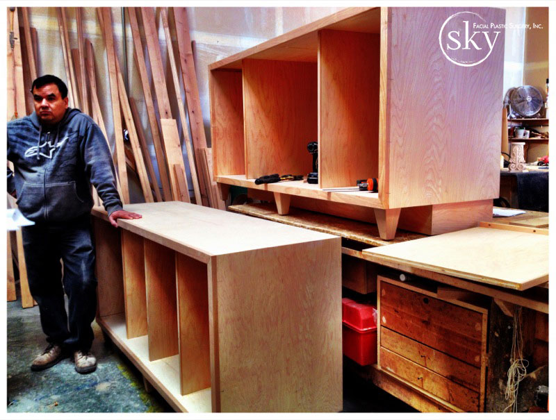 PHOTO: Crafstman standing next to credenza he is building.