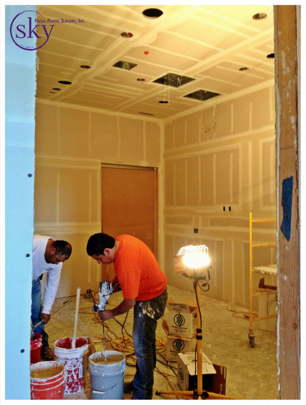 PHOTO: Two men mix plaster in the reception area.