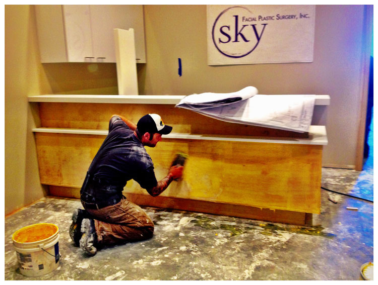 PHOTO: Man begins to install tile on front of reception desk.