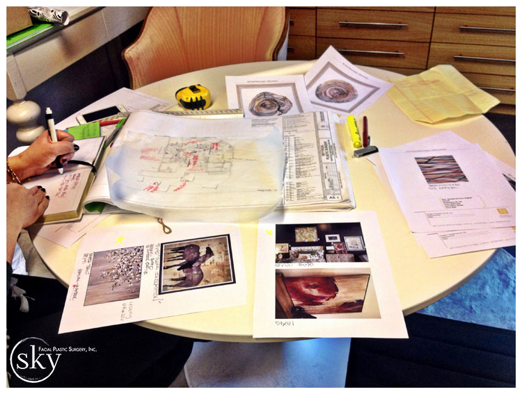 PHOTO: Table strewn with images of art and a space layout.
