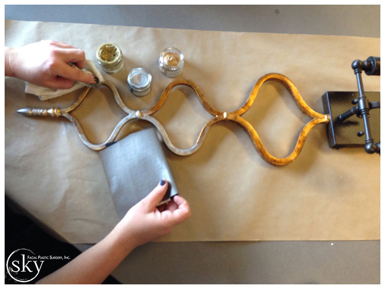 PHOTO: Hands applying metallic paint to sconce.