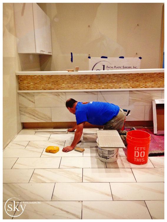 PHOTO: Man installing floor in lobby.
