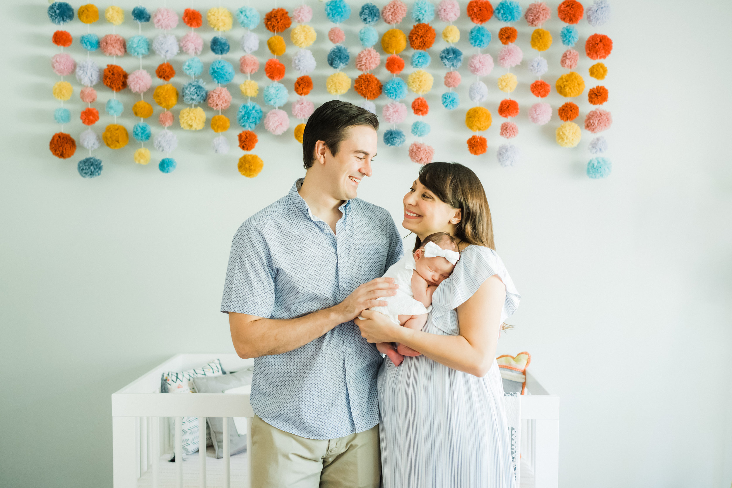 dallas newborn session. couple with baby girl in nursery, pom pom nursery wall display