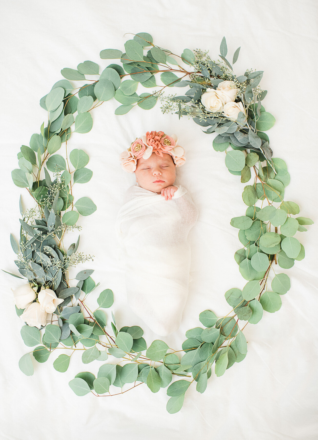dallas newborn photographer. Baby girl swaddled surrounded by greenery and florals