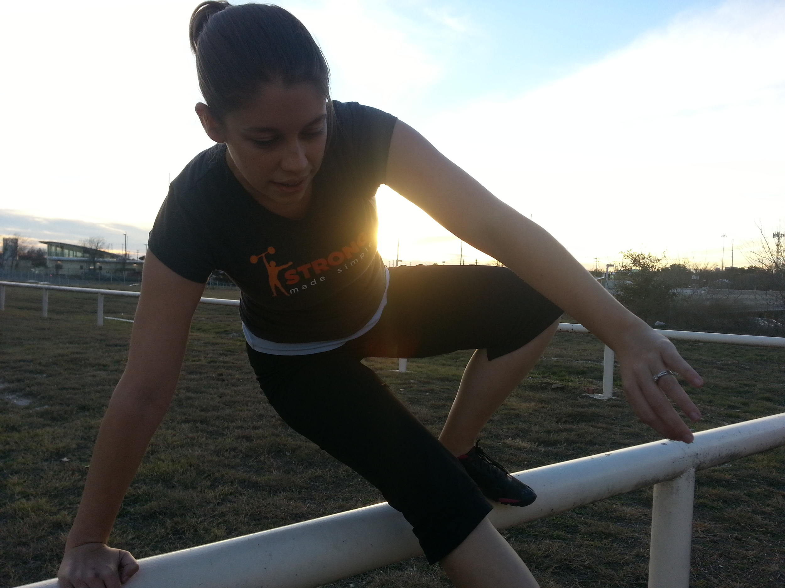 Personal training client, Tracy B., vaulting a fence.