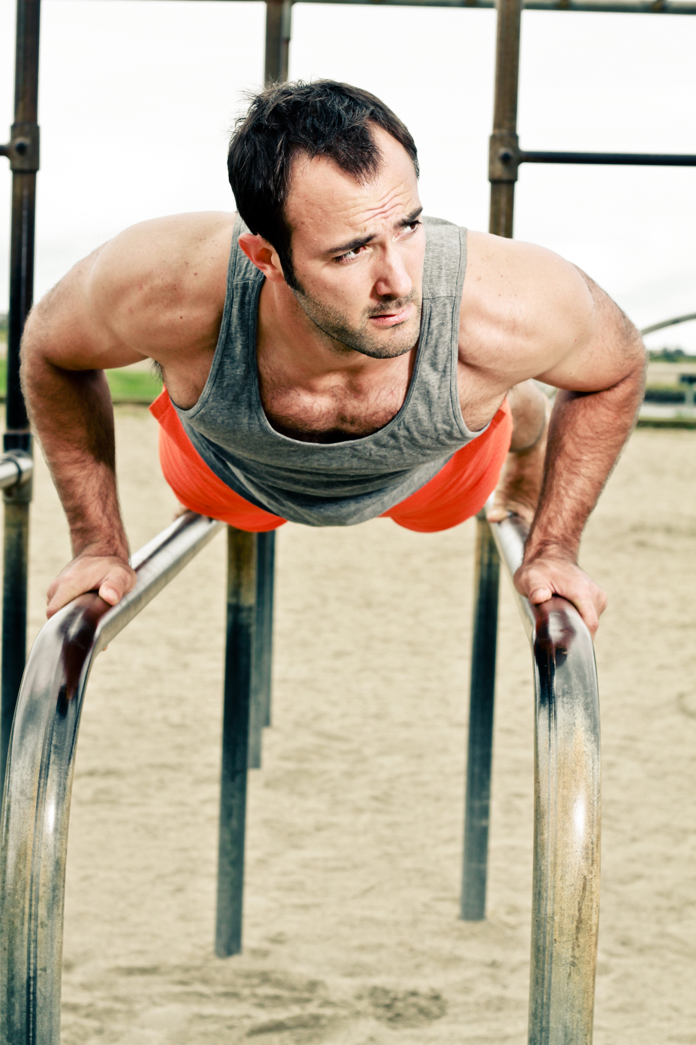 San Diego personal trainer, Brian Tabor, performs a push up outside on parallel bars.
