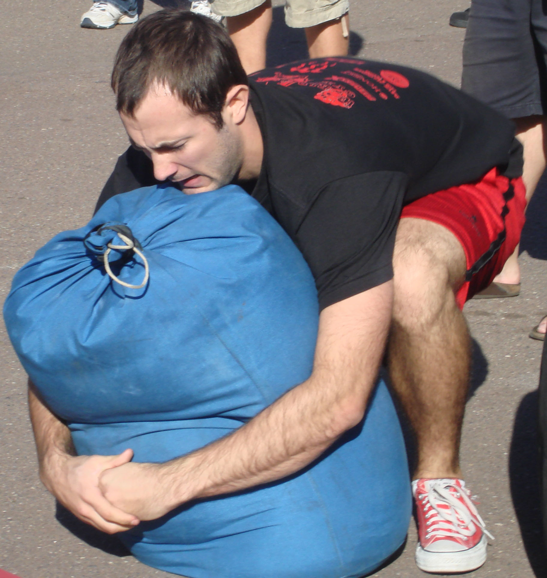 San Diego personal trainer, Brian Tabor, picks up a large sandbag without handles in a strongman competition.