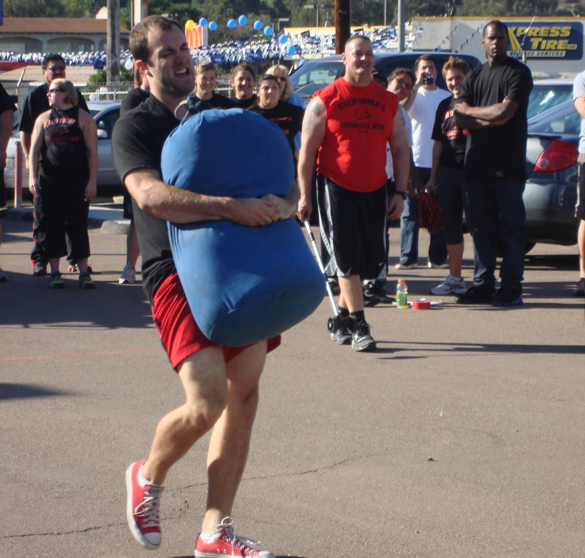 San Diego personal trainer performing a sandbag carry without handles in a strongman contest.