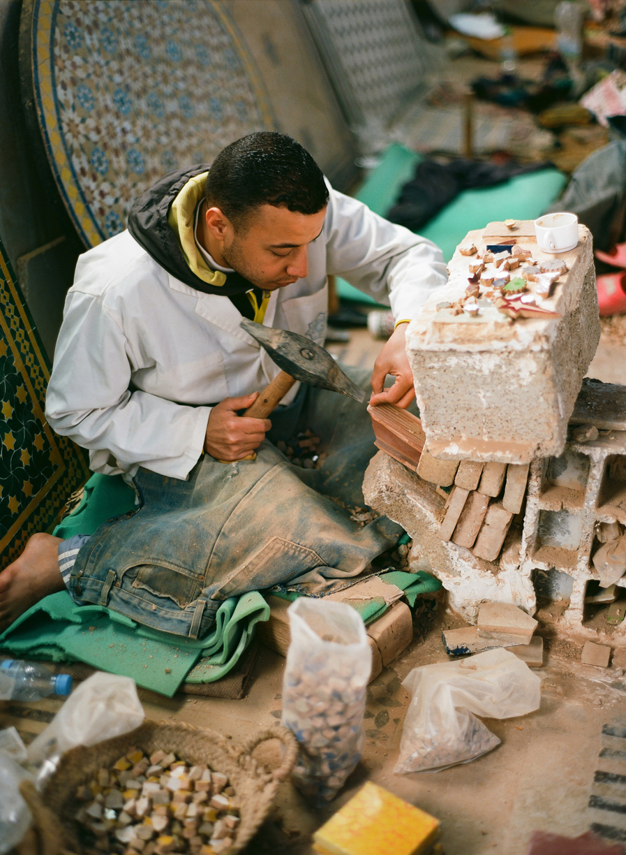man chiseling tile at co-op_fez_web.jpg