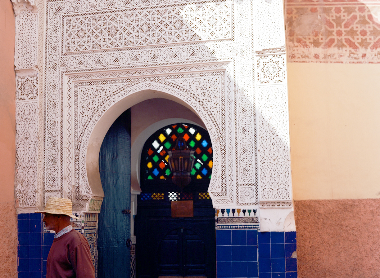 Man in straw hat walking out of doorway with multi-colored glass_Marrakech_web.jpg