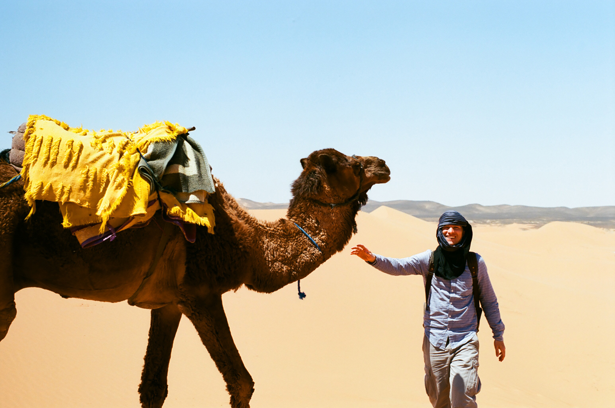 Cole smiling and walking towards camel_Sahara_web.jpg