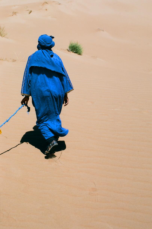 Camel Guide_Sahara Man Walking & Holding Line to Camels_web.jpg