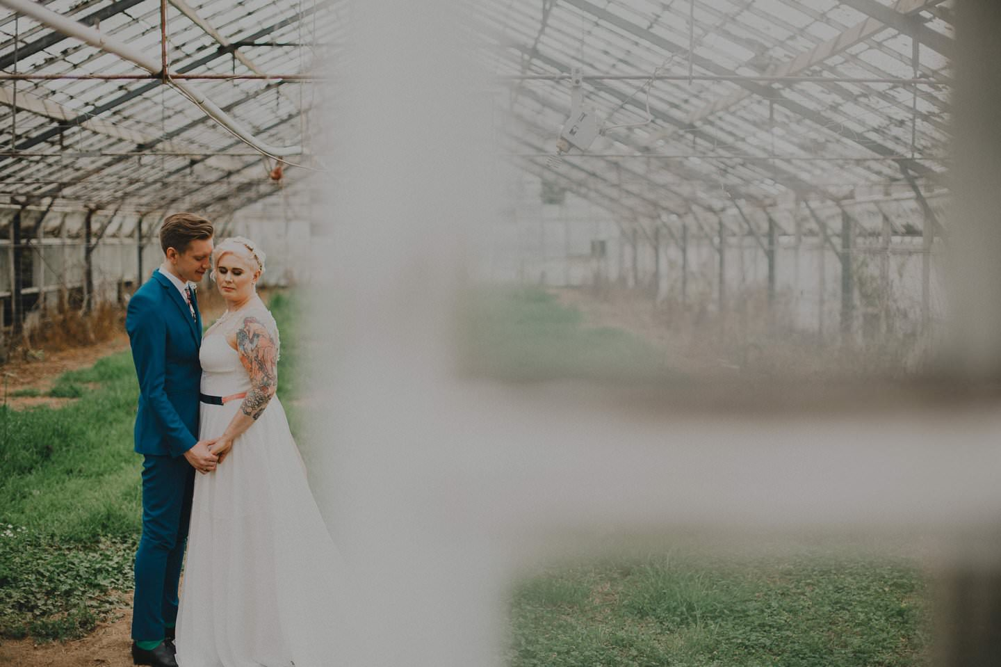 Artistic wedding photography of couple in a glass house