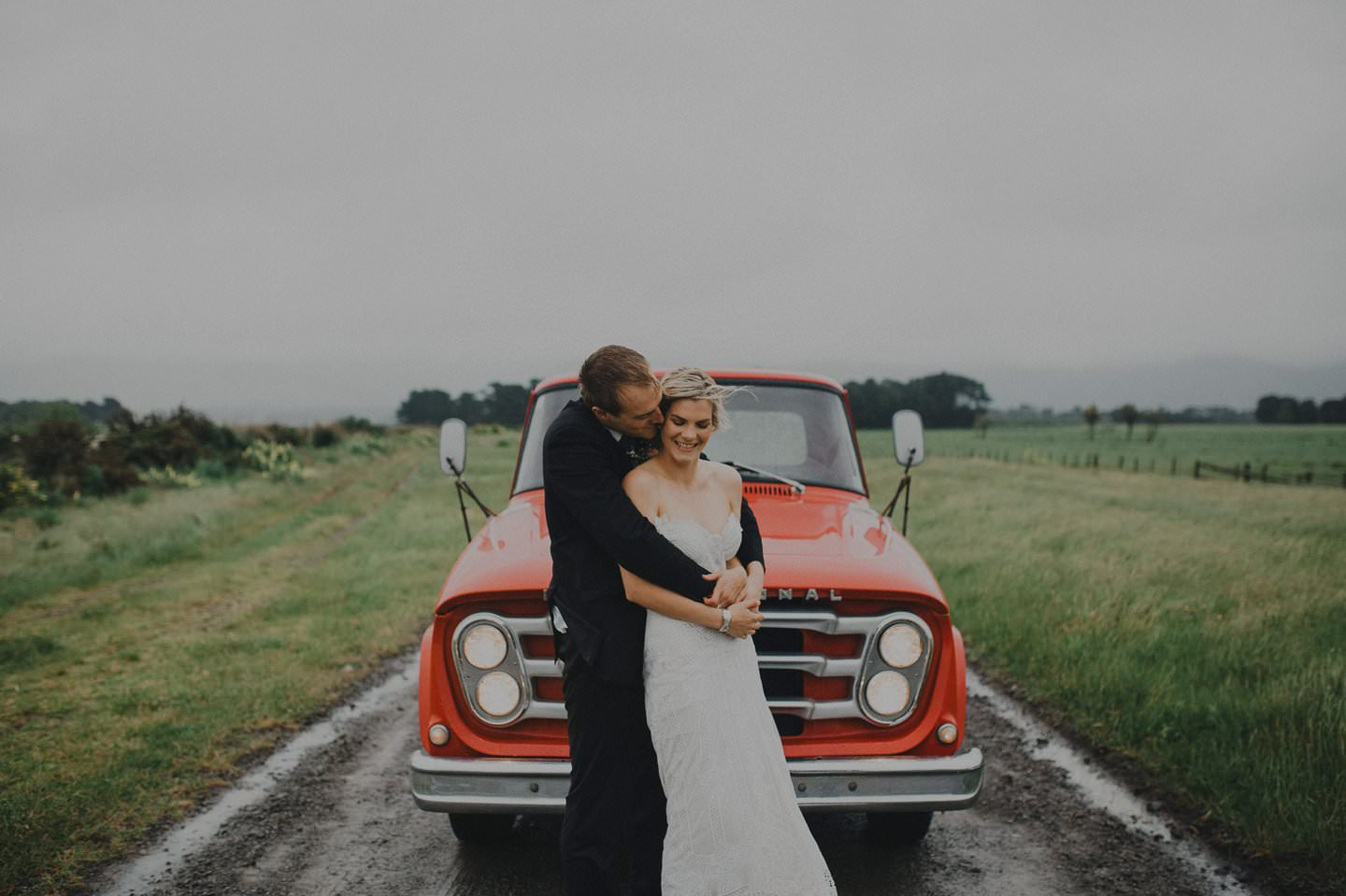 Dramatic wedding photo of bride and groom in the rain