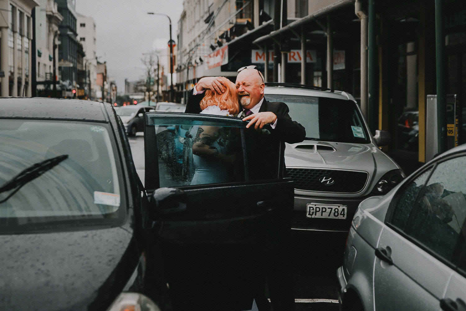 Emotional dad helping bride out of car