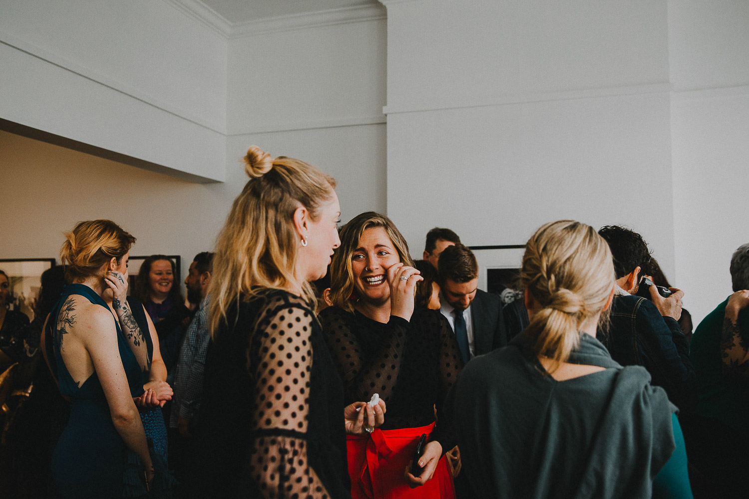 Guests mingling at modern art gallery wedding