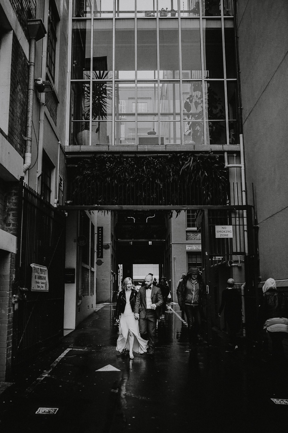 Adventurous couple walking in the rain in leeds street Wellington