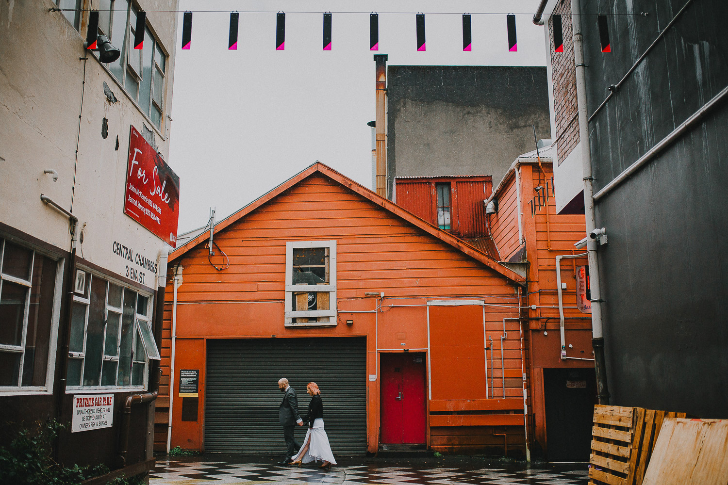 Wedding couple walking in the rain in Wellington ally way