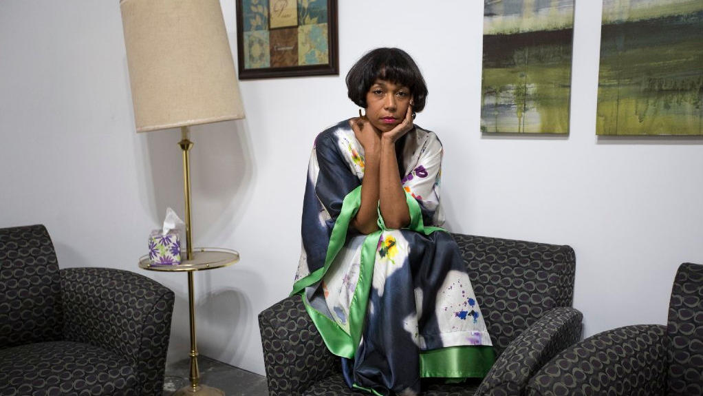 Artist Karon Davis poses in her installation, a re-creation of a hospital waiting room, at Wilding Cran Gallery in Los Angeles. (Brian van der Brug / Los Angeles Times)