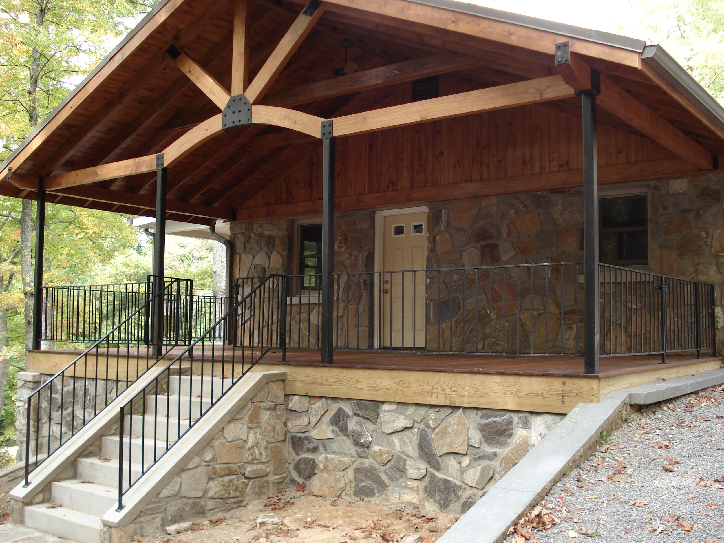 Sofa Rock Residence, Covered front porch with tongue and groove ipe flooring and custom metalwork on railings and supports for for roof.