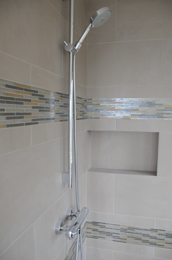 Porcelain tile shower with glass mosaic accents.