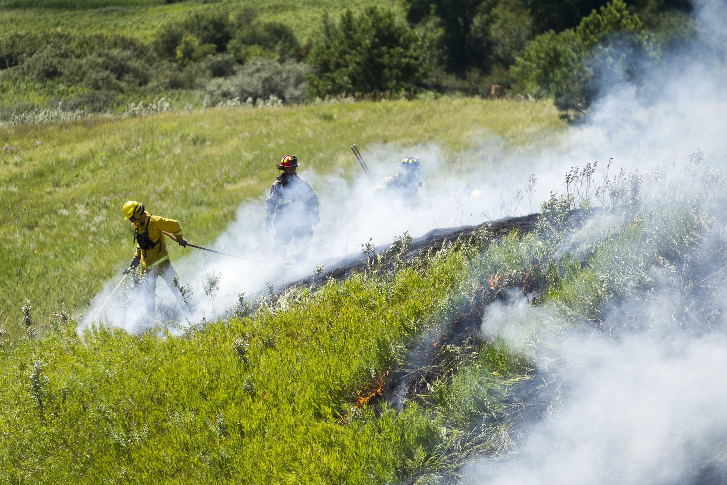 Firefighters extinguish a brushfire behind the Wal-Mart in Minot, ND.