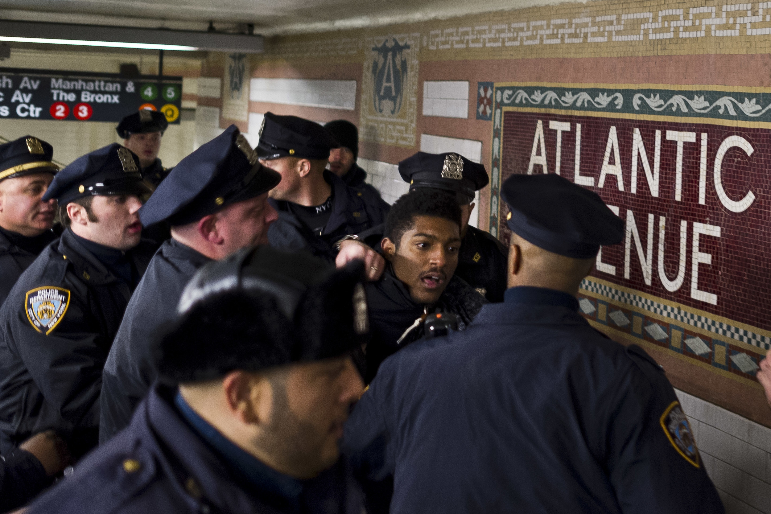 A dozen NYPD officers arrest a lone protestor after a heated standoff inside the Atlantic Avenue subway station in Brooklyn. 2014