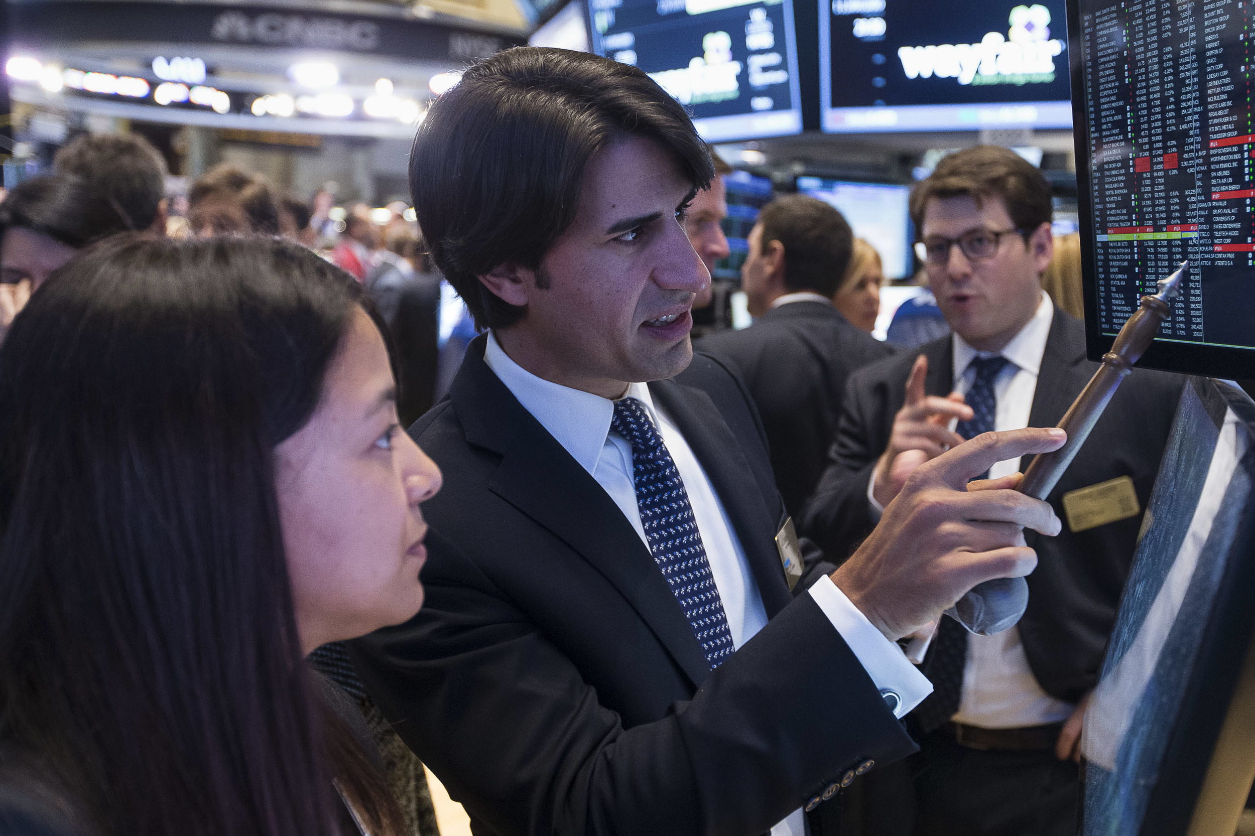 A CEO uses his ceremonial gavel to analyze numbers with his Designated Market Maker.