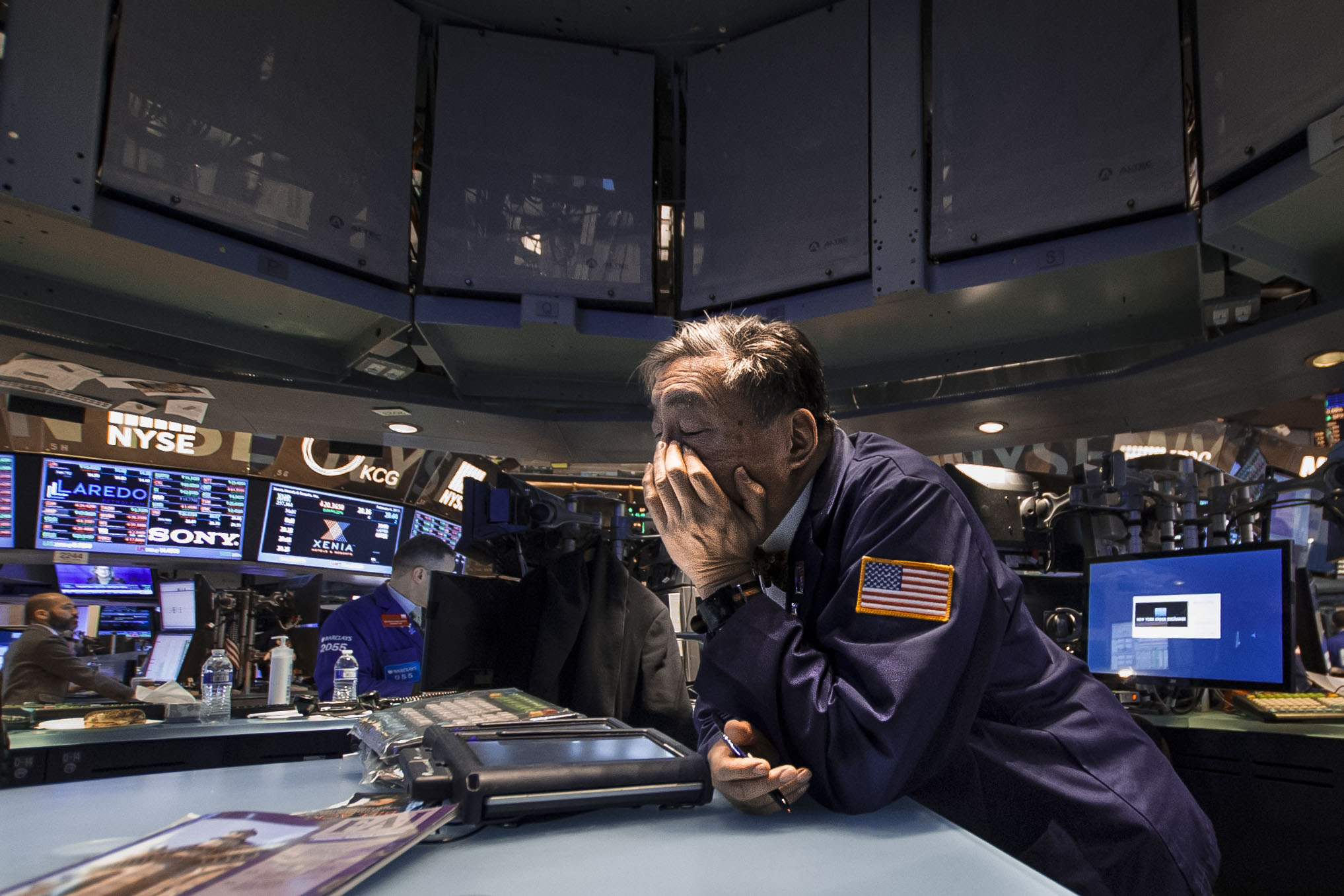 A floor trader rubs his eyes after a long day.