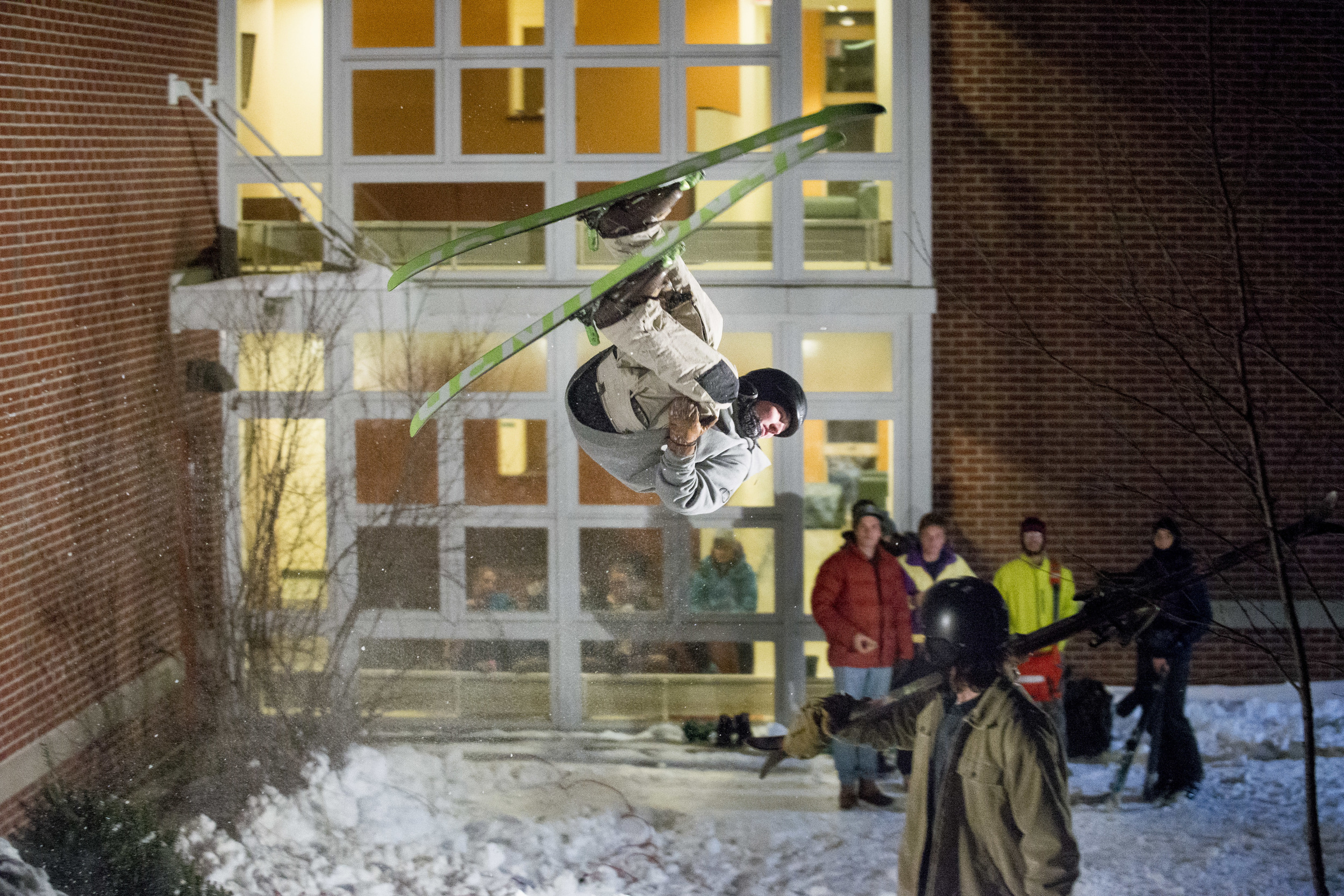 "Patrick Sheils '19 of Portland, Maine eyes the landing for his flip at the base of Mt. David. The Bates Shred Club hosts ""Skill 'N Grill,"" featuring a ski jump at the bottom of Mt. David behind 280 College Street as part of the 2016 Winter Carnival."