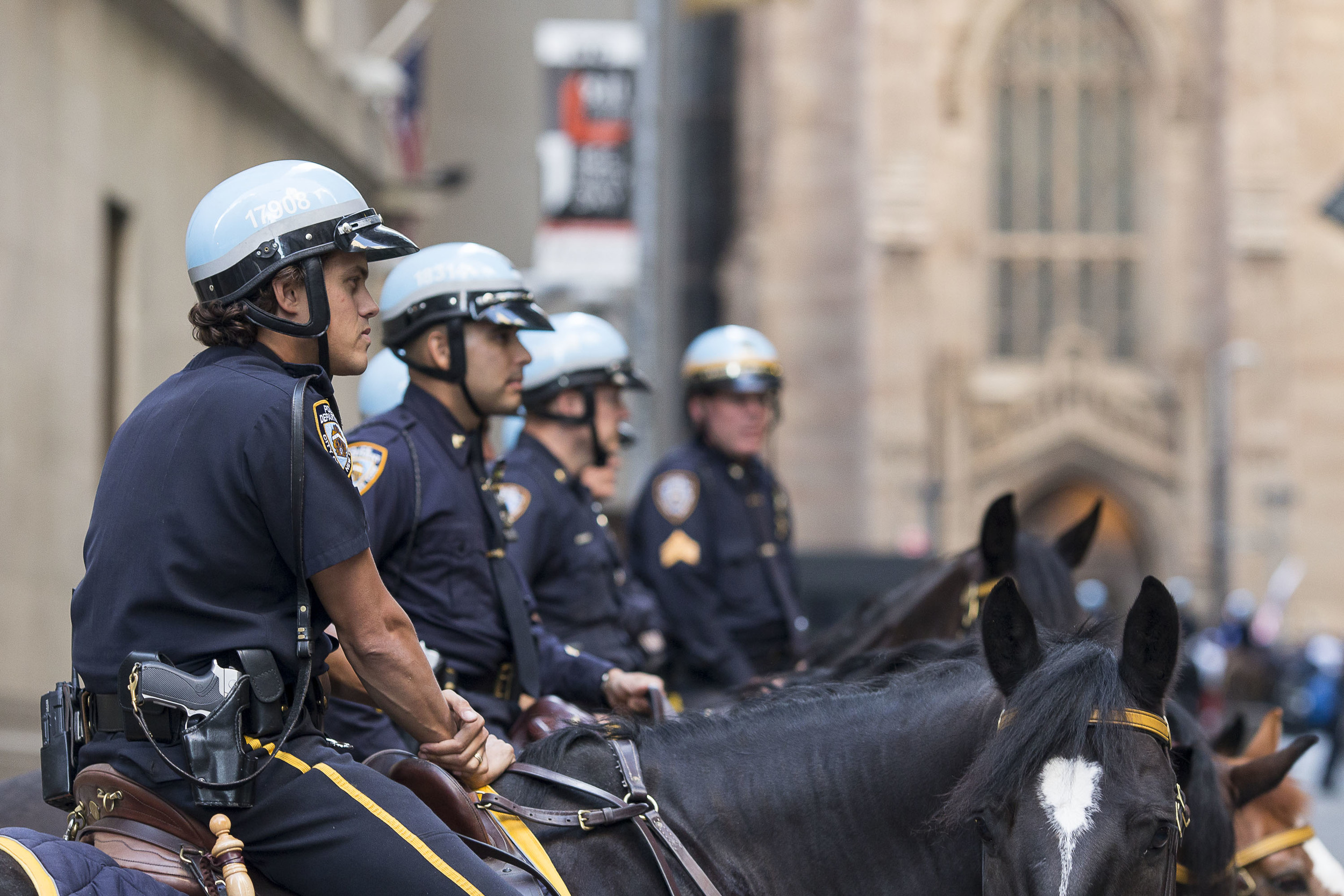 In anticipation of the protest, NYPD mounted patrolmen work to completely blockade the corner of Wall Street and Broad Street in front of the Stock Exchange.