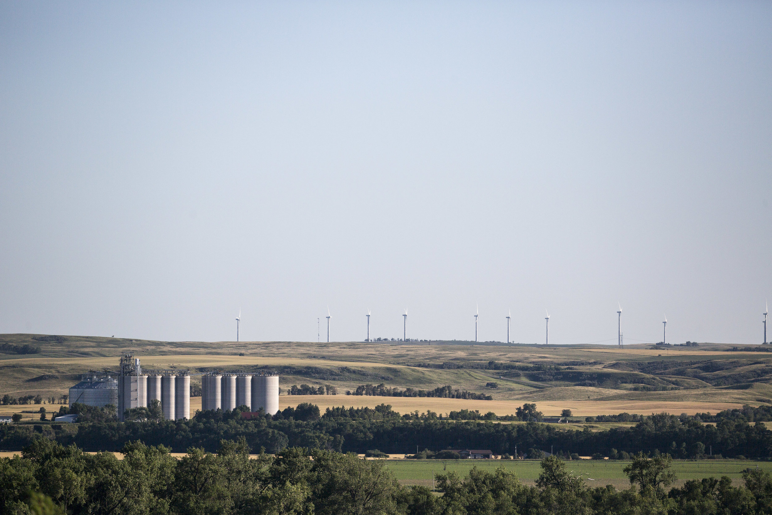 Granaries and distant windmills, looking southwest across the Missouri River from Washburn.