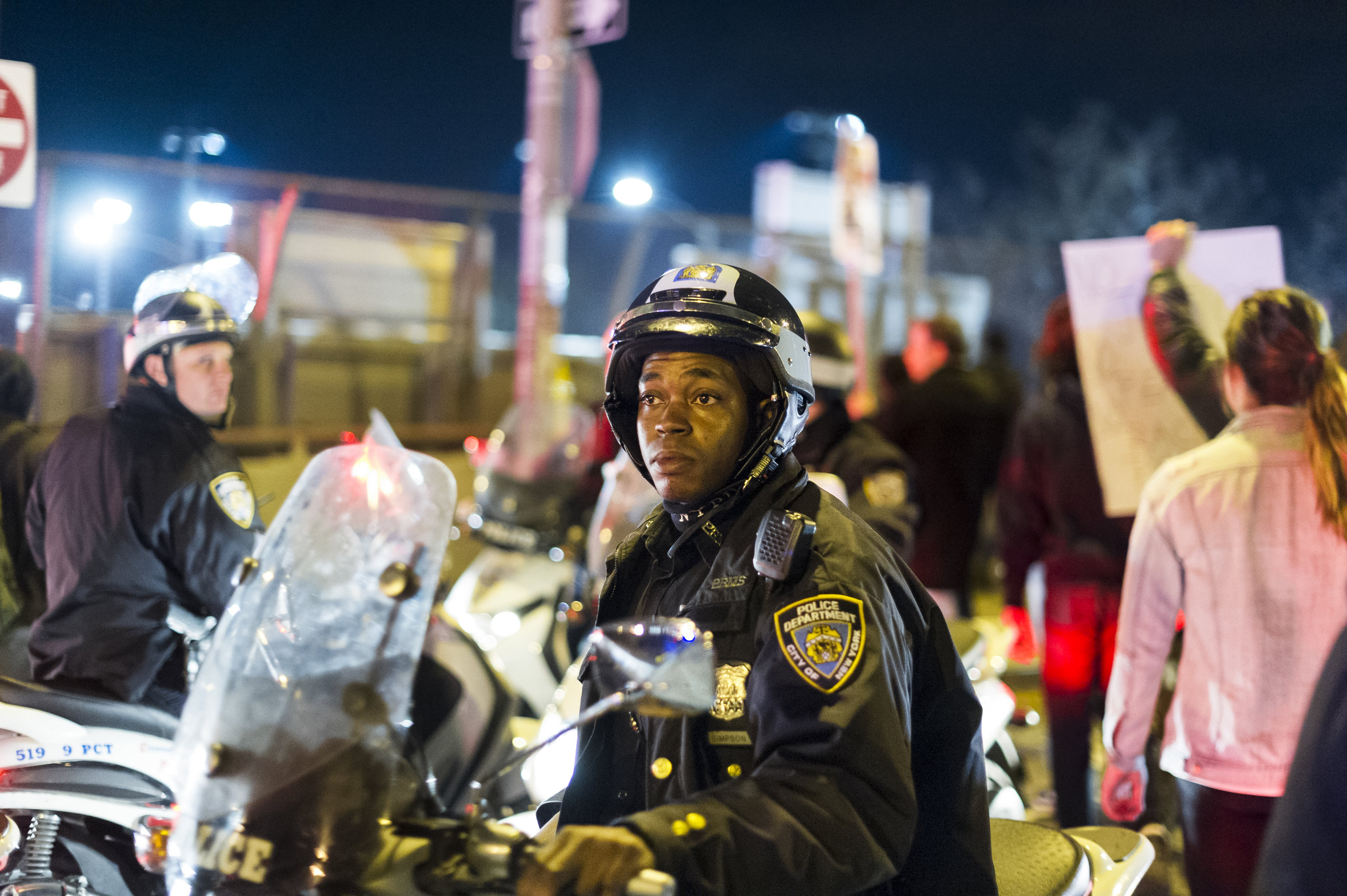 An NYPD officer looks on as FDR Drive is shut down by demonstrators on November 25th, 2014 following a St. Louis grand jury's decision to not indict Officer Darren Wilson in the killing of Michael Brown.