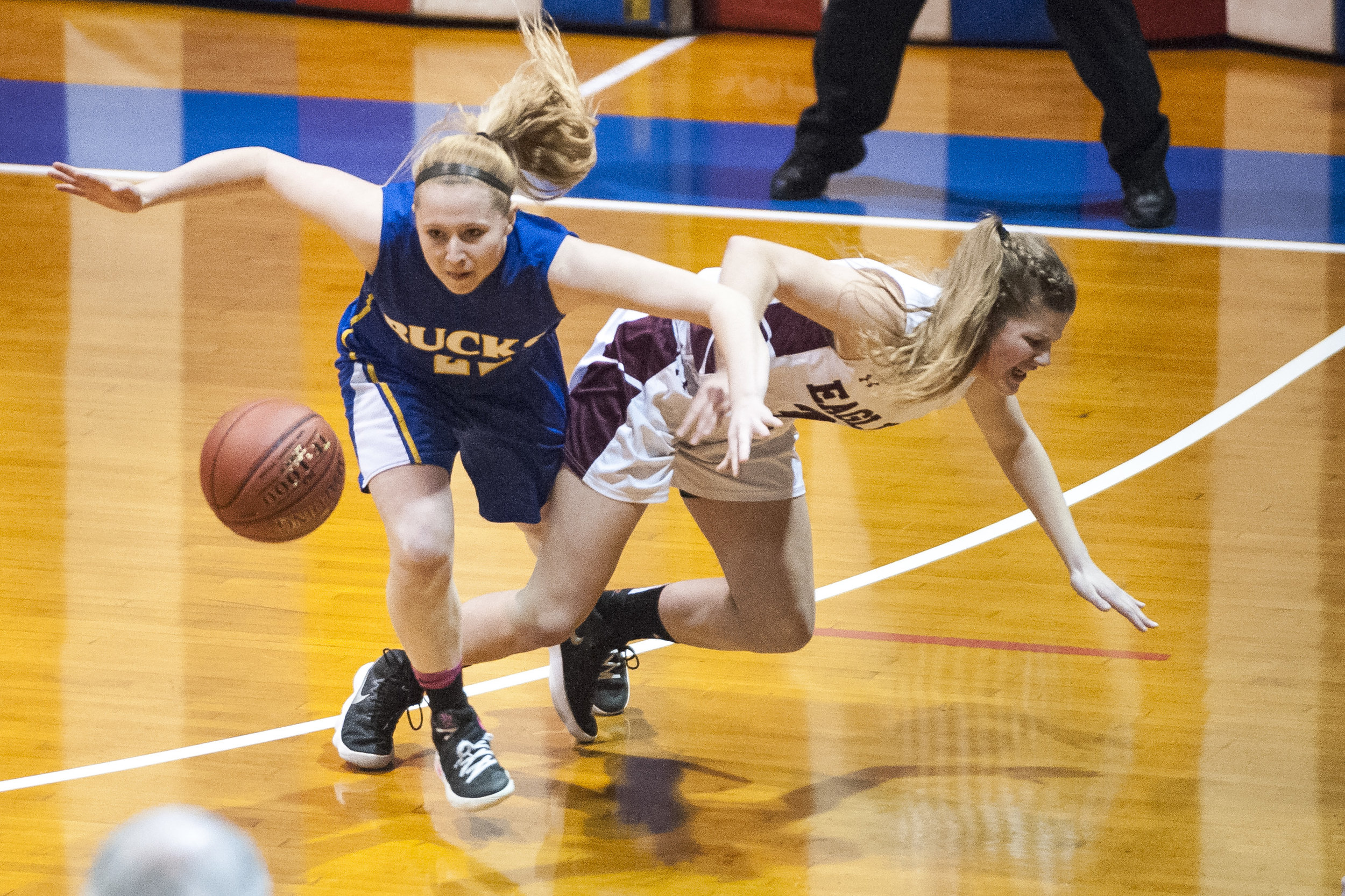 Blue Mountain Union's junior Annie Dennis (L) battles Arlington junior Kierstyn Hess (R) for a loose ball at the Barre Auditorium on Monday, March 5th 2018.
