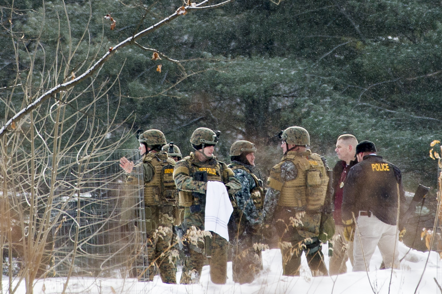 Vermont State Police officers gather after fatally shooting Nathan Giffin on the athletic fields at Montpelier High School on Tuesday, January 16th 2018. Giffin robbed at gunpoint the Vermont State Employees Credit Union adjacent to the school, where he was once a student. After a nearly-hour long standoff, during which Giffin made suicidal statements and threats, eight state troopers and one Montpelier Police officer opened fire, alleging that he moved toward them with the weapon. The weapon turned out to be a BB-gun.