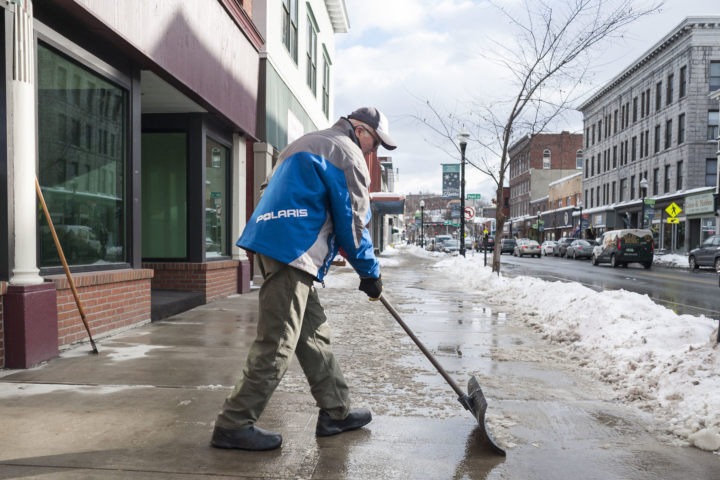 Derek Bartlett clears the sidewalk on Main Street in Barre on Tuesday, January 9th 2018. Warmer temperatures finally allowed Bartlett to finish clearing ice from previous storms during the cold snap.