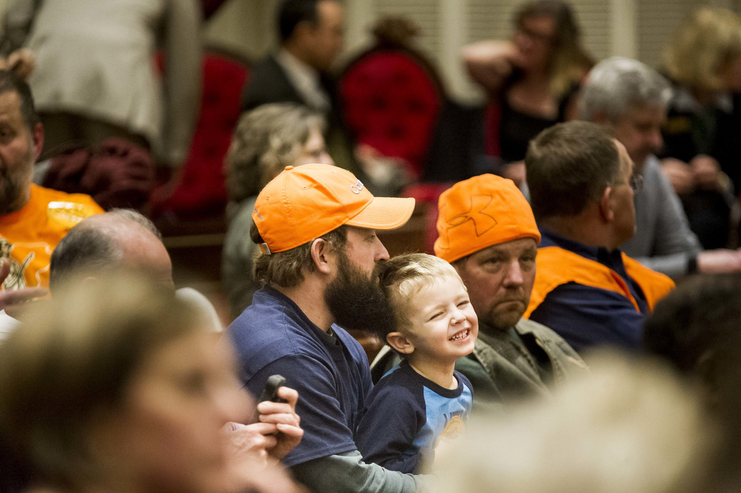 Kale Barberi of Marshfield talks with his son Gavin, 4, as groups opposed to new gun legislation, donning blaze orange apparel, turned out in high numbers to attend public hearings at the State House on Tuesday, January 30th 2018.