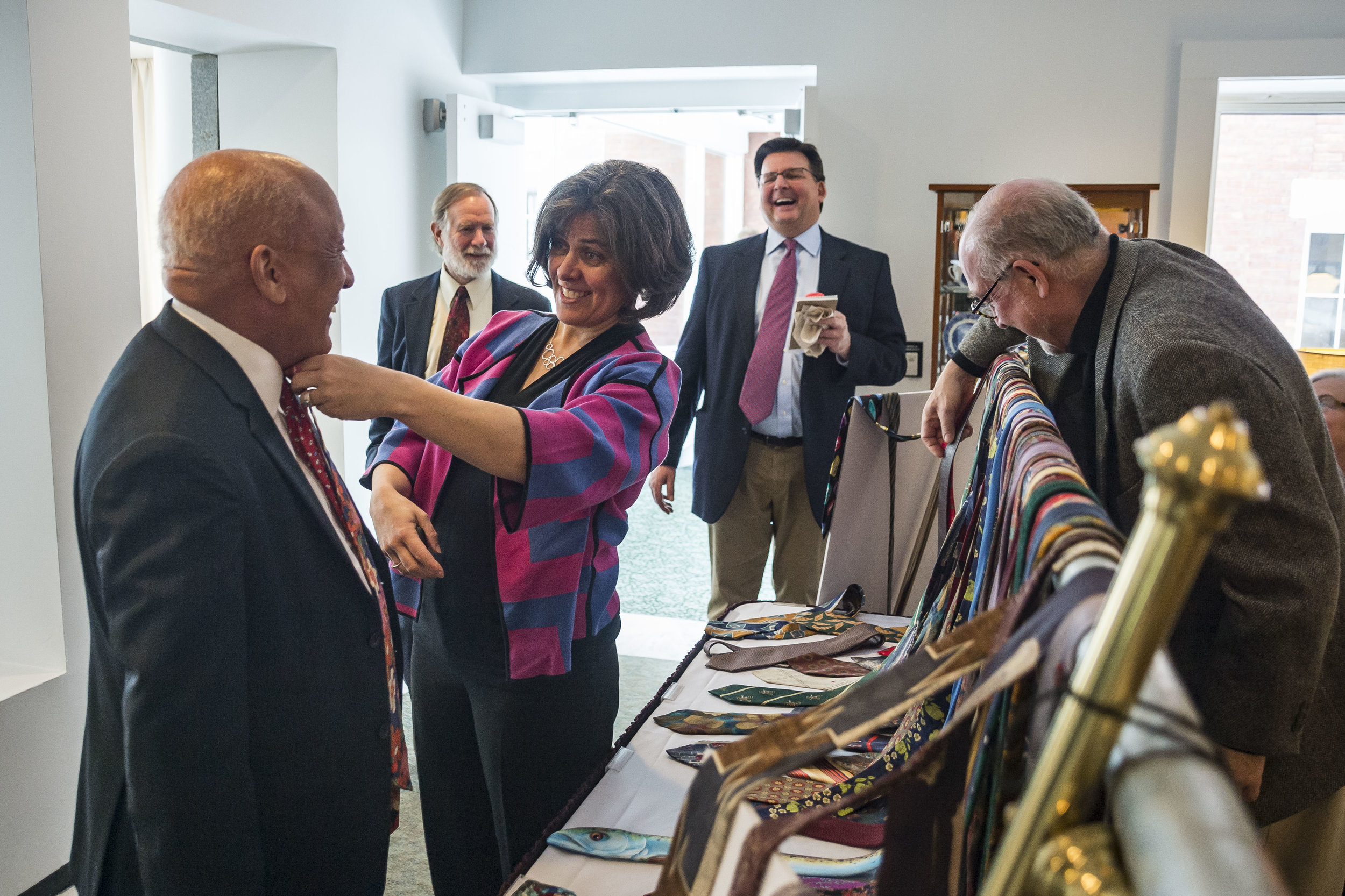 On April 17th, 2018, Vermont Speaker of the House Mitzi Johnson (pictured center) samples one of retiring representative David Sharpe's (D-Addison 4, pictured left rear) neckties on Senator Randy Brock (pictured left, R-Franklin). Sharpe is retiring at the conclusion of this year's session, and is selling numerous themed neckties he has worn throughout his legislative career to benefit Friends of the State House.