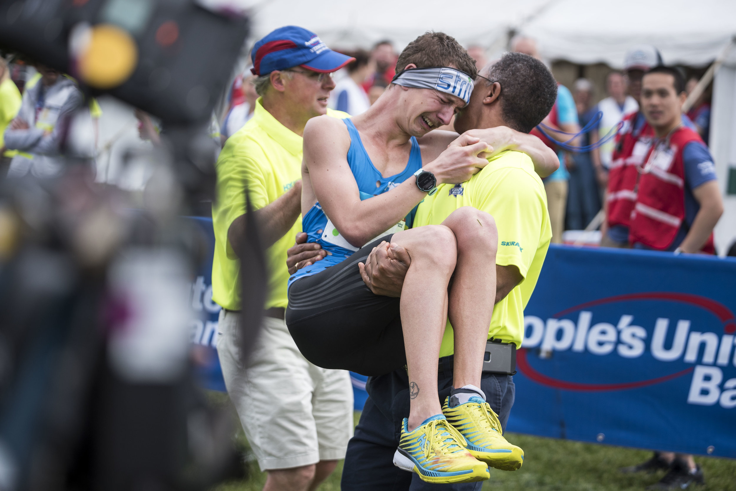 Tyler Andrews of Concord, MA finishes first (2:17:44) and is assisted by medical staff at the 30th People's United Bank Vermont City Marathon in Burlington on May 27th, 2018.